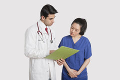 Doctor discussing medical report with female nurse over gray background Royalty Free Stock Images