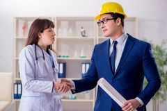 The doctor discussing new hospital plan with architect. Doctor discussing new hospital plan with architect royalty free stock photo