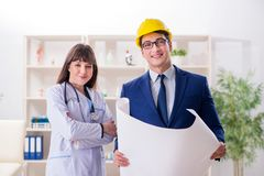 The doctor discussing new hospital plan with architect. Doctor discussing new hospital plan with architect stock photo