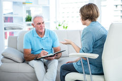 Doctor discussing with patient at home Royalty Free Stock Image