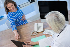 Doctor discussing with pregnant patient over digital tablet. At the hospital Royalty Free Stock Photography