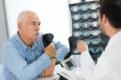 Doctor discussing x-ray scans elderly male patient. Doctor discussing x-ray scans of elderly male patient royalty free stock photo