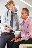 Doctor Discussing Records With Patient Using Digital Tablet Royalty Free Stock Images