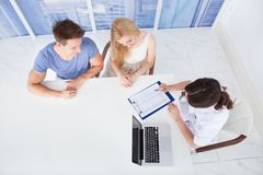Doctor discussing report with young couple in clinic Stock Photography