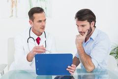 Doctor discussing reports with patient at medical office Stock Photography