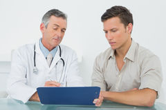 Doctor discussing reports with patient at office Stock Photography