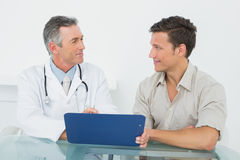 Doctor discussing reports with patient in office Royalty Free Stock Photo