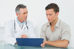 Doctor discussing reports with patient at office Stock Image