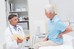 Doctor discussing reports with patient suffering from backache Royalty Free Stock Photography