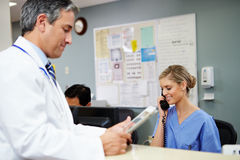 Doctor In Discussion With Nurse At Nurses Station Stock Photo