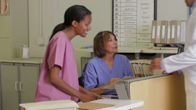 Doctor In Discussion With Nurse At Nurses Station Stock Image