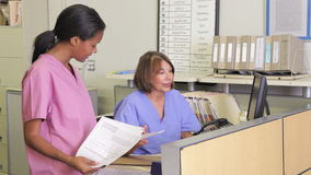 Doctor In Discussion With Nurse At Nurses Station Royalty Free Stock Photos