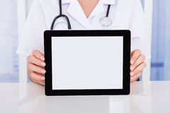 Doctor displaying digital tablet at desk. Midsection of female doctor displaying digital tablet at desk in hospital Royalty Free Stock Image
