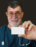Doctor Displays a Blank Business Card. A doctor holds up a blank business card. Focus on business card in foreground Royalty Free Stock Images
