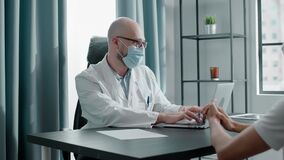 Doctor in disposable face mask talks to hospital visitor