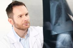 Doctor is watching an X-ray. A doctor in a doctor`s office is watching an x-ray of a patient stock image