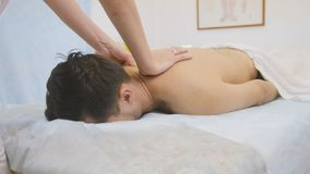 The doctor does massage back and shoulders the man at physiotherapy Stock Image