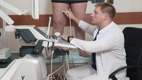 The doctor does ultrasound examination of the legs in the patient. A man with varicose veins came to the doctor for. Advice. Study by means of ultrasonic waves stock video