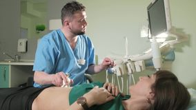Doctor doing 3d ultrasound on belly of t woman in clinic 4k stock footage