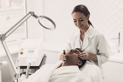 Doctor Doing Dermatology Procedure in Clinic. Smiling Young Doctor Doing Dermatology Procedure in Clinic. Cosmetologist in Modern Clinic. Professional of stock photography