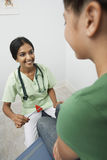Doctor Doing Flex Test On Girl. Happy female doctor examining girl with reflex hammer stock images
