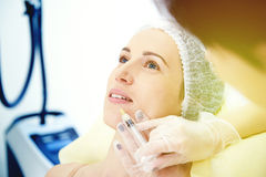 Doctor doing injecting. For lips augmentation royalty free stock image