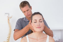 Doctor doing neck adjustment stock photography