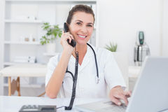Doctor doing phone call while she using computer Royalty Free Stock Photo