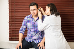 Doctor doing a physical exam to patient. Female doctor examining a patient`s ears using an otoscope during a routine checkup Stock Image