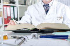 Doctor doing research in a medical book. At office Stock Image
