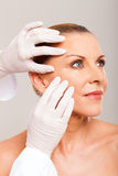 Doctor skin check. Doctor doing skin check on mid age woman face over white background Stock Photography