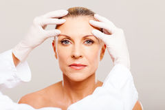 Senior cosmetic surgery. Doctor doing skin check on senior woman before cosmetic surgery Royalty Free Stock Photography