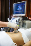 Doctor doing an ultrasound on a patient abdomen Royalty Free Stock Photography