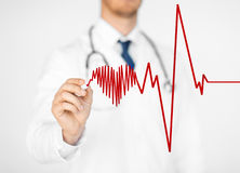 Doctor drawing electrocardiogram on virtual screen Royalty Free Stock Images