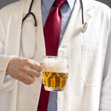 Doctor is drinking beer royalty free stock image