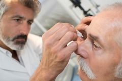 Doctor dripping eye drops to senior patient royalty free stock image