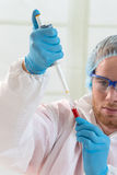 Doctor dropping blood samples i. Nto test tubes for analysis Stock Photo
