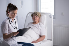 Doctor with elderly hospice patient stock images
