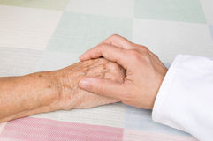 Doctor and elderly patient. Hand of a doctor holding the hand of an elderly patient Royalty Free Stock Images