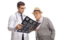 Doctor and an elderly patient looking at an x-ray scan. Isolated on white background stock images