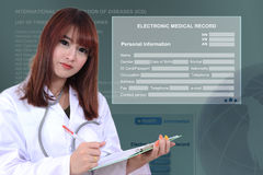 Doctor with electronic medical record. Female doctor working on patient medical record in front of electronic medical record background Royalty Free Stock Photo