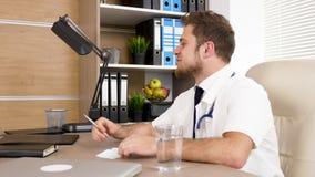 Doctor en el escritorio en oficina que habla con su colega y sonrisa metrajes