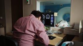 Doctor en el hospital que mira la exploración del CT metrajes