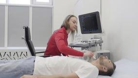 Doctor en el procedimiento del ultrasonido para la tiroides de diagnóstico en el paciente masculino metrajes