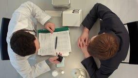 Doctor en el teléfono con el paciente en el hospital Visión superior imagen de archivo
