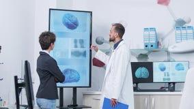 Doctor en el traje blanco en el centro de investigaci?n m?dico que muestra una simulaci?n del cerebro 3D a un paciente almacen de metraje de vídeo