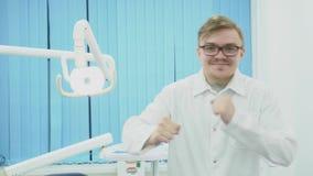 Doctor en la capa blanca feliz y el baile media Dentista en la capa blanca y los vidrios que bailan feliz de trabajo excelente metrajes
