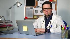 Doctor en la capa blanca que se sienta en gabinete y que trabaja en su ordenador portátil metrajes