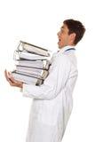 Doctor en la tensión con las pilas de ficheros. Burocracia Foto de archivo libre de regalías