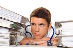 Doctor en la tensión con las pilas de ficheros. Burocracia Fotografía de archivo libre de regalías